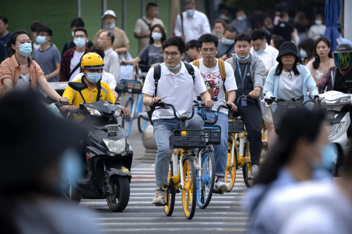 """People ride bicycles across an intersection during rush hour in Beijing, Friday, July 2, 2021. A small but visible handful of urban Chinese are rattling the ruling Communist Party by choosing to """"lie flat,"""" or reject high-status careers, long work hours and expensive cities for a """"low-desire life."""" That clashes with party ambitions to make China a wealthier consumer society. (AP Photo/Mark Schiefelbein)"""