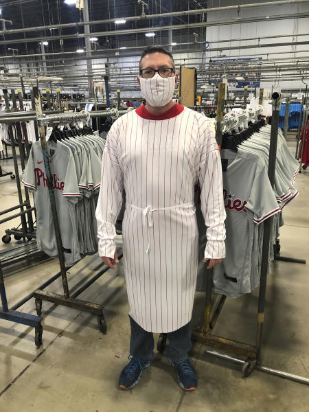 This image provided by Fanatics, shows a model wearing a protective mask and gown for medical professionals made from the fabric of a baseball uniform. Fanatics, the company that manufactures uniforms for Major League Baseball in Pennsylvania, has suspended production on jerseys and is instead using the polyester mesh fabric to make masks and gowns that help fill the dearth of protective wear at hospitals in Pennsylvania and nearby states. (Fanatics via AP)