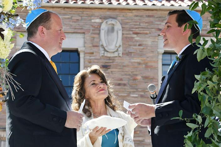 In this photo provided by Jocelyn Augustino, Rabbi Tirzah Firestone, center, officiates a traditional Jewish wedding ceremony attended by family and friends for Colorado Gov. Jared Polis, left, and his partner, Marlon Reis, in Boulder, Colo. on Wednesday Sept. 15.