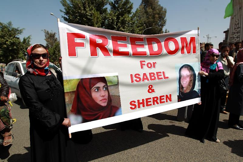 Yemeni women hold a banner calling for the release of French hostage Isabelle Prime (right image) and her Yemeni interpreter Sherine Makkaoui (left image) during a rally in Sanaa, on March 5, 2015 (AFP Photo/Mohammed Huwais)