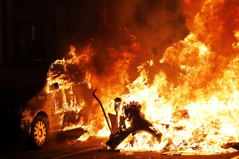 A car catches fire next to a burning barricade during clashes between protestors and police in Barcelona, Spain, Wednesday, Oct. 16, 2019. Spain's government said Wednesday it would do whatever it takes to stamp out violence in Catalonia, where clashes between regional independence supporters and police have injured more than 200 people in two days. (AP Photo/Bernat Armangue)
