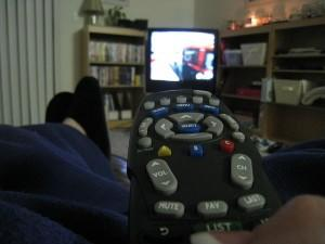 TV remote pointed at screen, with feet up