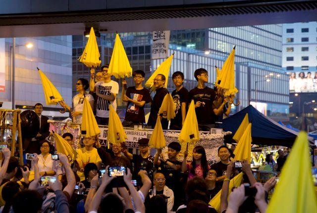 Protesters, including Joshua Wong, carry yellow umbrellas at an Umbrella Movement demonstration in Hong Kong in October 2014.