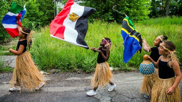 PHOTO: In this June 19, 2018, file photo, girls wave flags as they march along Pasadena Avenue in a parade from Max Brandon Park to University Park, celebrating Juneteenth in Flint, Mich. (Jake May/The Flint Journal via AP, FILE)
