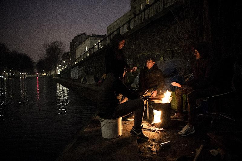 Migrants, mostly from Afghanistan, keep warm around a fire at a  makeshift camp set up along the canal Saint-Martin in Paris on March 19, 2018. EU countries registered 650,000 requests for asylum last year, half the number from 2016