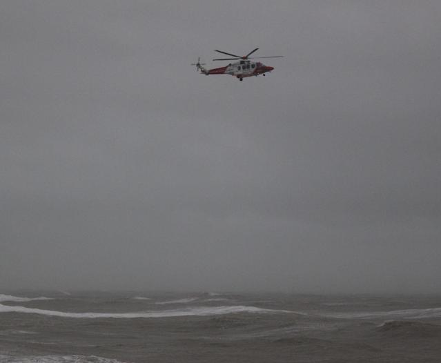 A Coastguard helicopter off the coast of Hastings searching for a missing surfer, who was later found safe (Picture: PA)