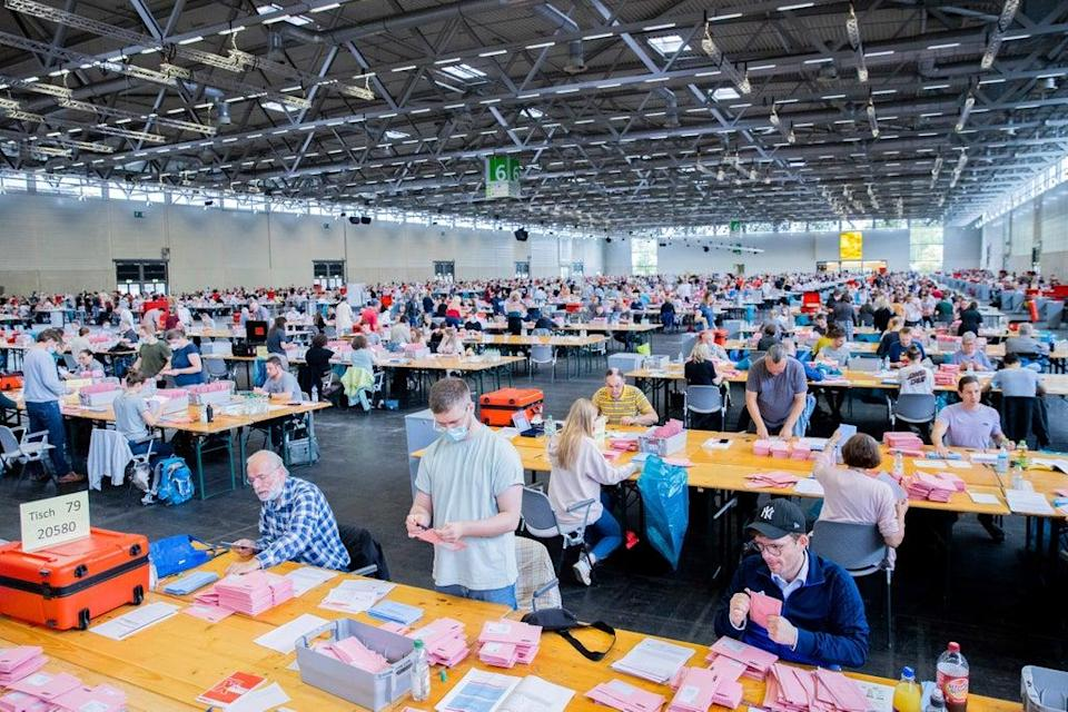 Election workers open the pink envelopes during the counting of the postal vote for the Germany parliament election, in Cologne, Germany (AP)
