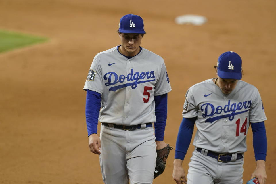 Los Angeles Dodgers shortstop Corey Seager (5) and Enrique Hernandez walk off the field after Game 4 of the baseball World Series Saturday, Oct. 24, 2020, in Arlington, Texas. Rays defeated the Dodgers 8-7 to tie the series 2-2 games. (AP Photo/Eric Gay)
