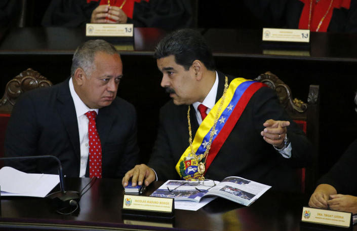 Venezuelan President Nicolas Maduro, right, speaks with Constitutional Assembly President Diosdado Cabello at the Supreme Court during an annual ceremony that marks the start of the judicial year in Caracas, Venezuela, Thursday, Jan. 24, 2019. Cabello and other high-ranking allies pledged to stand behind Maduro and denounced Juan Guaido who declared himself interim president on Wednesday. (AP Photo/Ariana Cubillos)