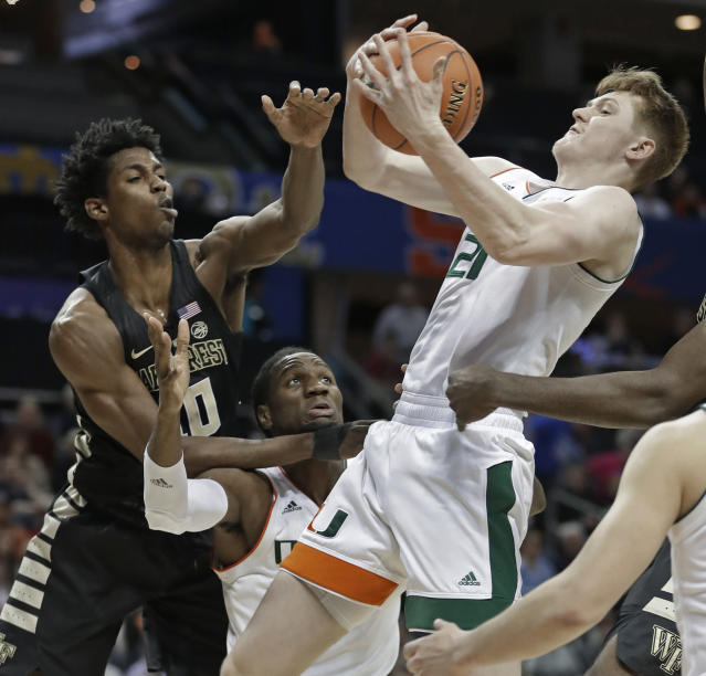 Miami's Sam Waardenburg (21) and Wake Forest's Jaylen Hoard (10) battle for a rebound during the first half of an NCAA college basketball game in the Atlantic Coast Conference tournament in Charlotte, N.C., Tuesday, March 12, 2019. (AP Photo/Nell Redmond)