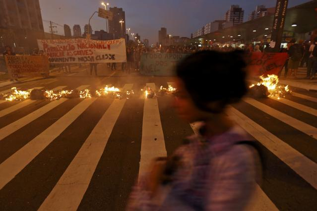A morning commuter rushes past protesters outside the closed entrance of Ana Rosa subway station during the fifth day of metro worker's protest in Sao Paulo June 9, 2014. Subway workers went on strike in Sao Paulo for a fifth day on Monday even after a court ruled the stoppage illegal, spreading chaos across Brazil's biggest city just days ahead of the opening match of the World Cup soccer tournament. REUTERS/Damir Sagolj (BRAZIL - Tags: SOCCER SPORT WORLD CUP TRANSPORT)