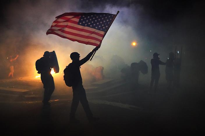 A protester holds an American flag aloft while walking through tear gas.