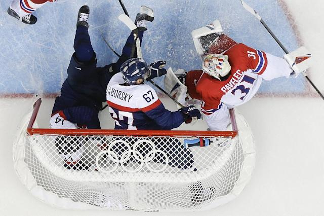 Slovakia defenseman Andrej Meszaros (14), Slovakia forward Tomas Zaborsky (67) and Czech Republic goaltender Ondrej Pavelec (31) crash into the net during the first period of the 2014 Winter Olympics men's ice hockey game at Shayba Arena, Tuesday, Feb. 18, 2014, in Sochi, Russia. (AP Photo/Matt Slocum)