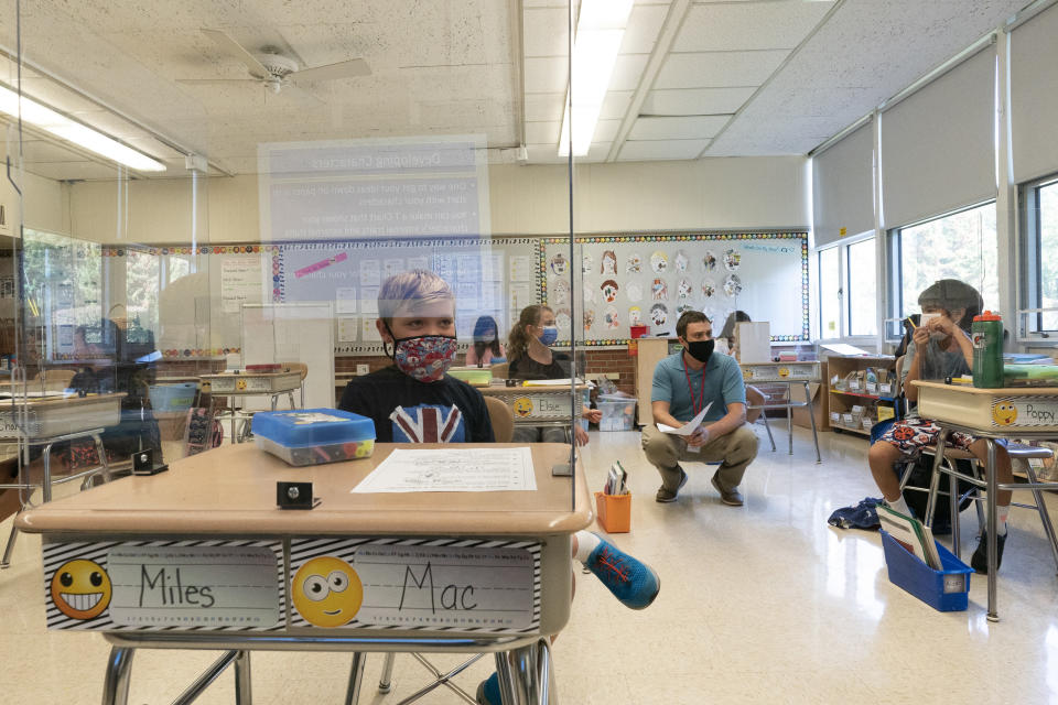 Students sit behind plexiglass at their desks during the coronavirus outbreak as Brian Scarano teaches a fourth grade English class at the Osborn School, Tuesday, Oct. 6, 2020, in Rye, N.Y. (AP Photo/Mary Altaffer)