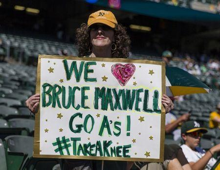 Sep 24, 2017; Oakland, CA, USA; Nancy Levine from Marin County holds up a sign in support of Oakland Athletics catcher Bruce Maxwell (not shown) before a game against the Texas Rangers at Oakland Coliseum. Mandatory Credit: John Hefti-USA TODAY Sports