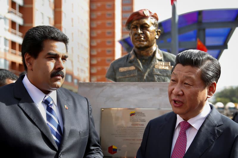 FILE PHOTO: China's President Xi speaks with Venezuela's President Maduro in front of a statue of Venezuela's late president Chavez during a ceremony in Caracas
