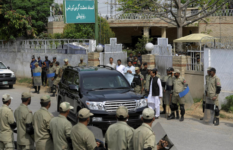 Paramilitary troops stand guard as a vehicle carrying Pakistan's former President and military ruler Pervez Musharraf leaves an anti-terrorism court in Rawalpindi, Pakistan, Tuesday, April 23, 2013. Musharraf appeared before the anti-terrorism court over the assassination of former prime minister Benazir Bhutto's case, officials said. (AP Photo/Anjum Naveed)