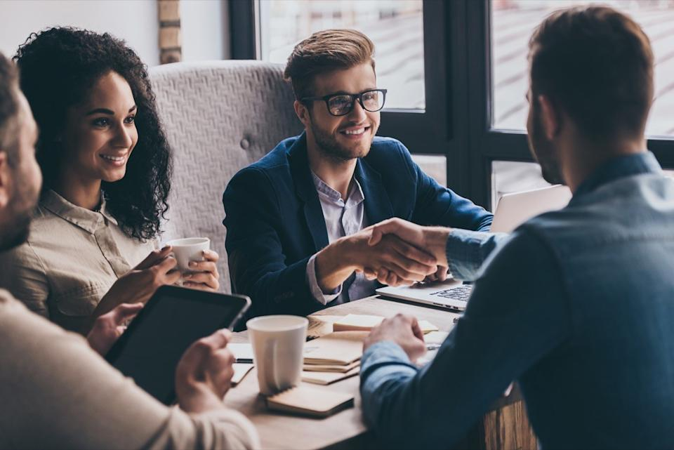 man shaking hands with bosses across a conference room, rude behavior