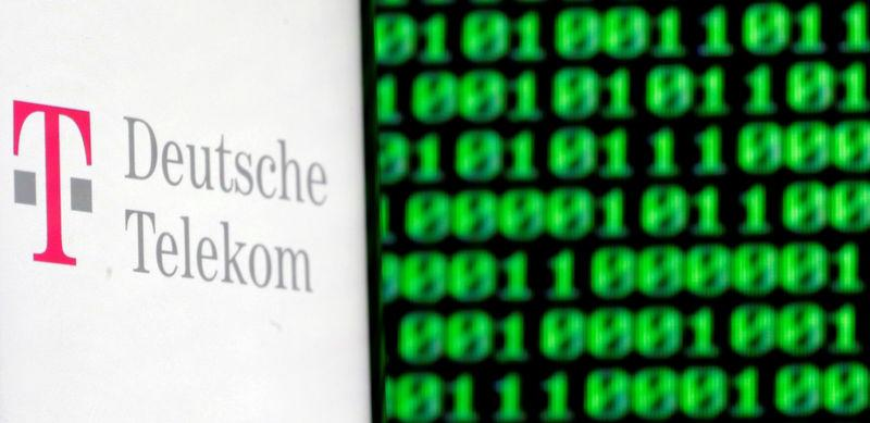 FILE PHOTO: A photo illustration shows a German Deutsche Telekom logo on smartphone in front of a displayed cyber code