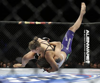 Ronda Rousey takes down Alexis Davis during their women's bantamweight title fight. (AP)