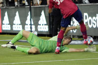 Los Angeles FC goalkeeper Tomas Romero, bottom, stops a shot from Dallas FC defender Justin Che during the first half of an MLS soccer match Wednesday, June 23, 2021, in Los Angeles. (AP Photo/Marcio Jose Sanchez)