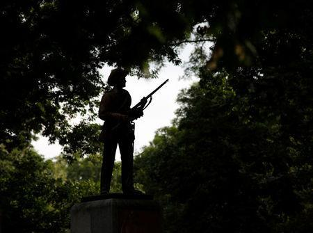 A statue of a Confederate soldier nicknamed Silent Sam is silhouetted on the campus of the University of North Carolina in Chapel Hill, North Carolina, U.S. August 17, 2017. REUTERS/Jonathan Drake