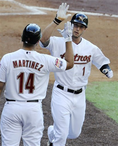 Houston Astros' Jordan Schafer (1) is congratulated by teammate J.D. Martinez (14) after hitting a solo homer in the first inning against the Colorado Rockies in a baseball game Saturday, April 7, 2012, in Houston. (AP Photo/Pat Sullivan)