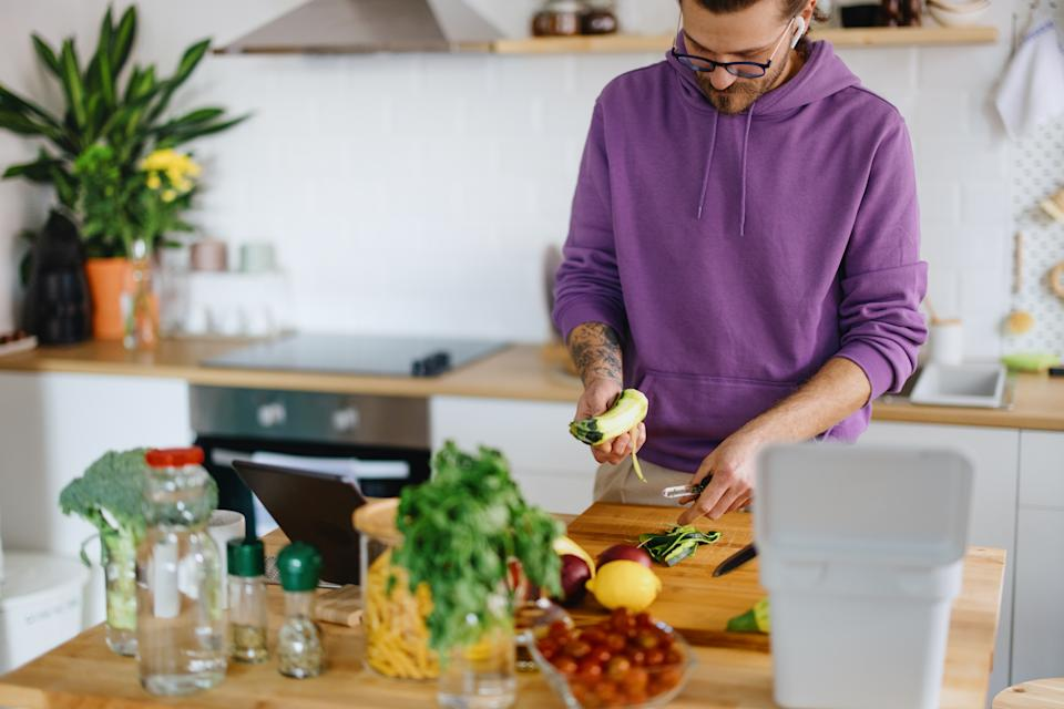 Young man cooks at home, preparing healthy vegetarian meal, using digital phone and tablet for recipe and video call with a friend