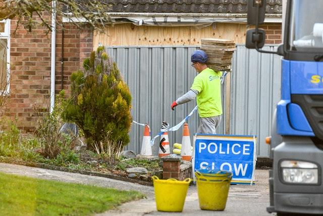 Contractors carry wooden scaffolding planks outside the home of former Russian spy Sergei Skripal in Salisbury