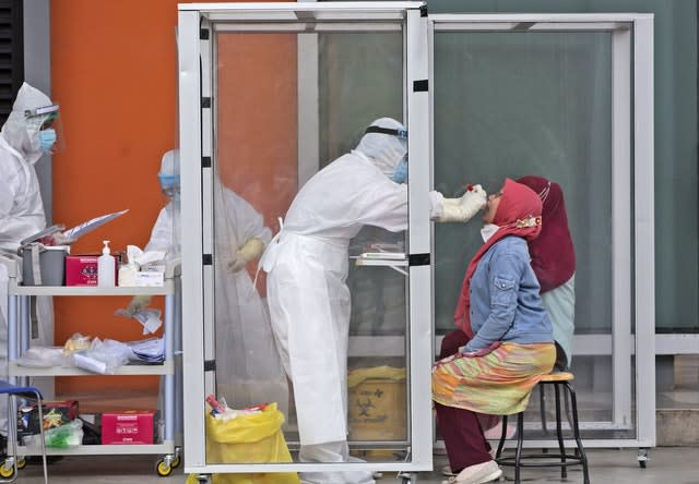 A medical worker collects samples from a woman during a mass test in North Sumatra, Indonesia (Binsar Bakkara/AP)
