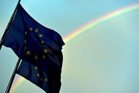 A rainbow is seen behind European flags during a euro zone EU leaders emergency summit in Brussels