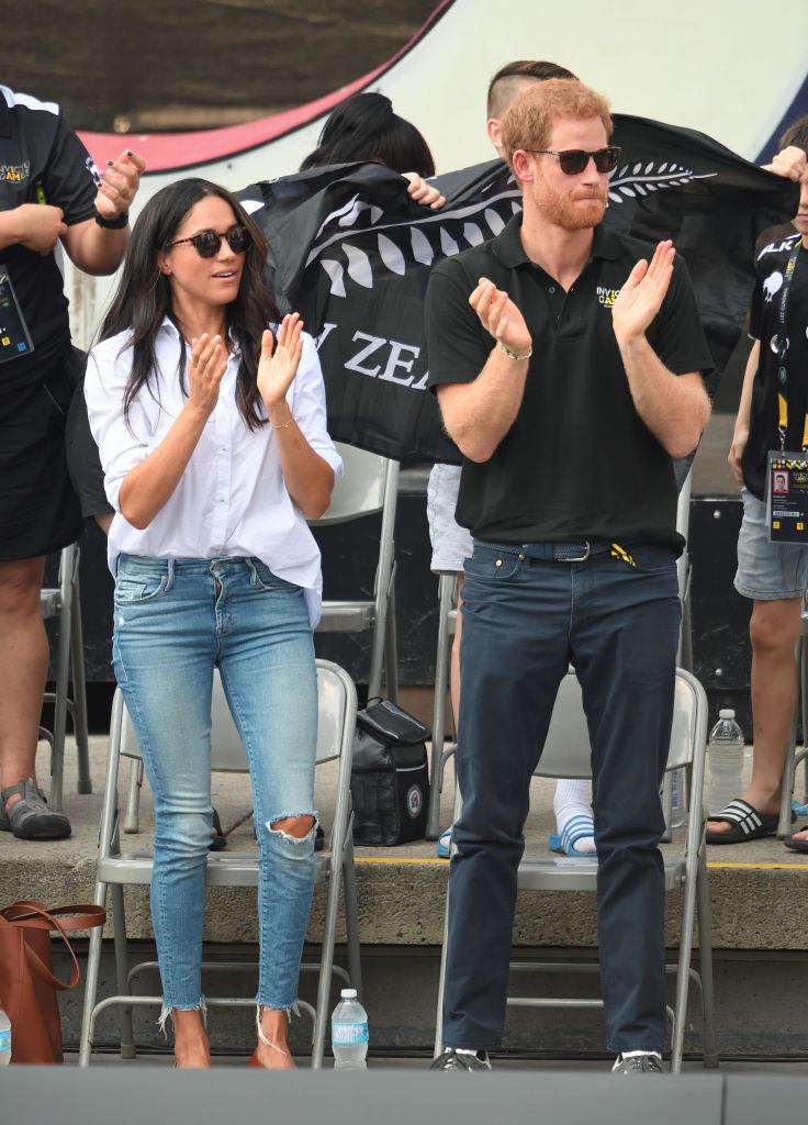 """<p>Markle made her public debut with Prince Harry at the 2017 Invictus Games in Toronto. Markle looked casual cool in a white <a href=""""https://fave.co/3t4cqsw"""" rel=""""nofollow noopener"""" target=""""_blank"""" data-ylk=""""slk:button down shirt by Misha Nonoo"""" class=""""link rapid-noclick-resp"""">button down shirt by Misha Nonoo</a> and a pair of <a href=""""https://fave.co/38FUcGj"""" rel=""""nofollow noopener"""" target=""""_blank"""" data-ylk=""""slk:ripped jeans by Mother denim"""" class=""""link rapid-noclick-resp"""">ripped jeans by Mother denim</a>. <em>(Image via Getty Images)</em></p>"""