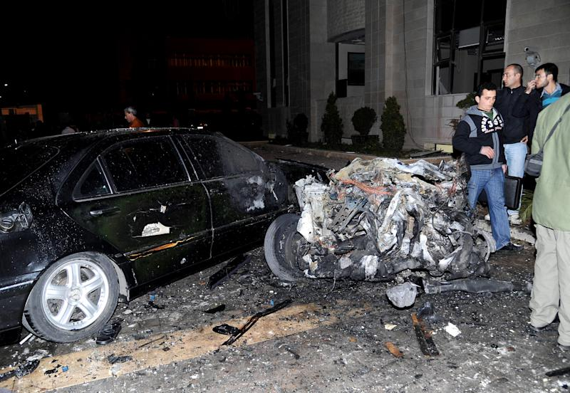In this Wednesday, Dec. 12, 2012 photo released by the Syrian official news agency SANA, People stand near a damaged car and debris after explosions hit the main gate of the Syrian Interior Ministry in Damascus, Syria. Three bombs collapsed walls in the Syrian Interior Ministry building Wednesday in Damascus, killing several, as rebels fighting to overthrow President Bashar Assad edged closer to the capital, the symbol of his power. (AP Photo/SANA)