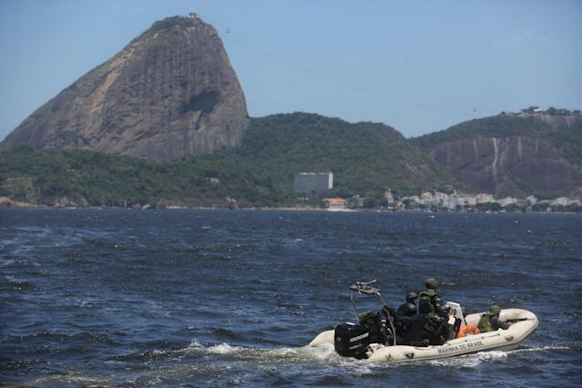 """Brazilian marines sail past Sugar Loaf mountain in a speed boat during a military exercise in Guanabara Bay, in Rio de Janeiro, Brazil, Wednesday, Feb. 20 2014. Brazil's Navy said that the operations being carried out this week in preparation for the 2014 FIFA World Cup are the largest exercises in its history. FIFA director of security Ralf Mutschke has said that FIFA is satisfied with the level of security that will be provided by Brazilian authorities, and guarantees that football's governing body """"is highly committed to ensuring the safety and security for fans, players and any other stakeholder involved in our event."""" (AP Photo/Leo Correa)"""
