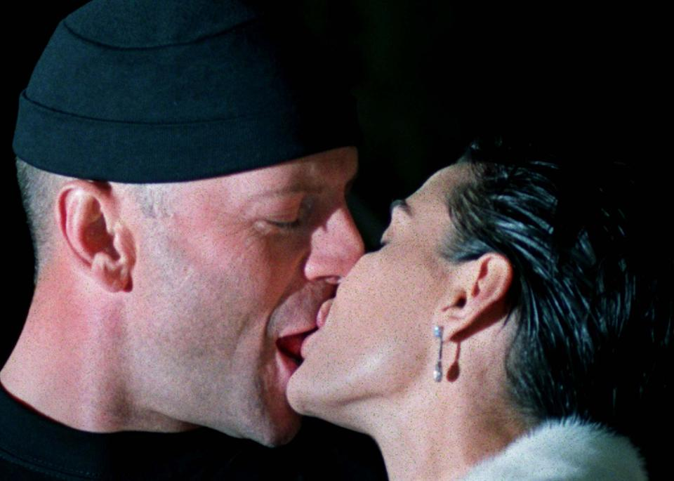 """American actor Bruce Willis (L) kisses his wife Demi Moore (R) at the opening of one of their new hamburger-restaurants, May 8. Willis attends the 50th Cannes Film Festival where he stars in French director Luc-Besson's """"Le Cinquieme Element"""" which was screened yesterday at the opening of the festival."""
