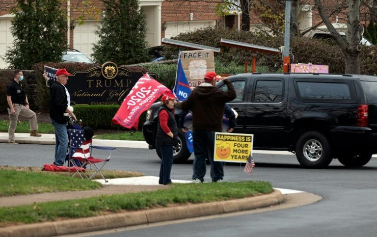 Supporters of -- and protesters against -- outgoing President Donald Trump watch his motorcade pass into the Trump International Golf Club in Sterling, Virginia on Saturday