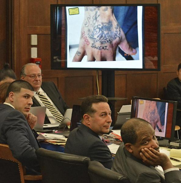 From left, with a photograph of former New England Patriots football player Aaron Hernandez's right hand projected behind them, defense attorneys Jose Baez and Ronald Sullivan listen to assistant district attorney Mark Lee during Hernandez's double murder trial in Suffolk Superior Court in Boston on Friday, March 17, 2017. Hernandez is on trial for the July 2012 killings of Daniel de Abreu and Safiro Furtado who he encountered in a Boston nightclub. The former NFL player is already serving a life sentence in the 2013 killing of semi-professional football player Odin Lloyd. (Chris Christo/The Boston Herald via AP, Pool)