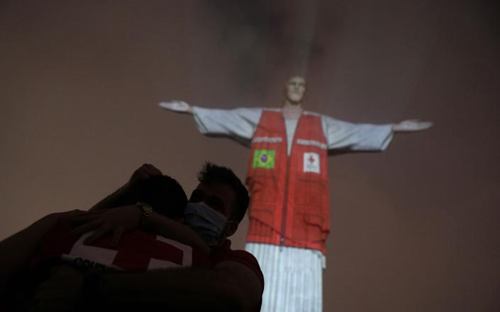 Members of the Red Cross embrace as a Red Cross volunteer vest is projected on the Christ the Redeemer statue to pay tribute to their assistance to Brazilians during the coronavirus disease outbreak, in Rio de Janeiro, Brazil - Reuters