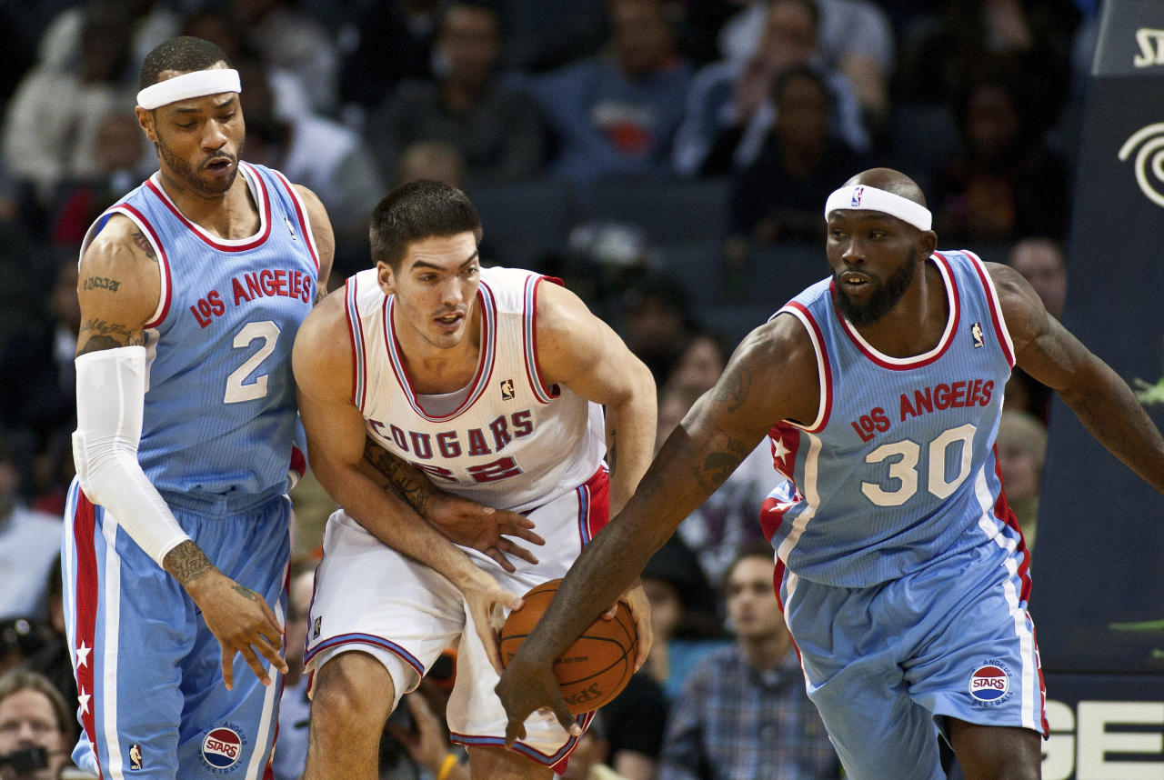 Charlotte Bobcats center Byron Mullens (C) works to control the ball against Los Angeles Clippers power forward Reggie Evans (30) and power forward Kenyon Martin (2) during their NBA basketball game in Charlotte, North Carolina February 11, 2012. Both teams, the Los Angeles Stars and Carolina Cougars, are wearing retro uniforms for the game. REUTERS/Chris Keane (UNITED STATES - Tags: SPORT BASKETBALL)
