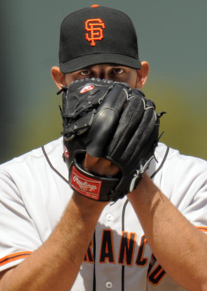 San Francisco Giants starting pitcher Madison Bumgarner looks over his glove for the call against the Colorado Rockies during the first inning of a baseball game on Thursday, April 12, 2012, in Denver. (AP Photo/Jack Dempsey)