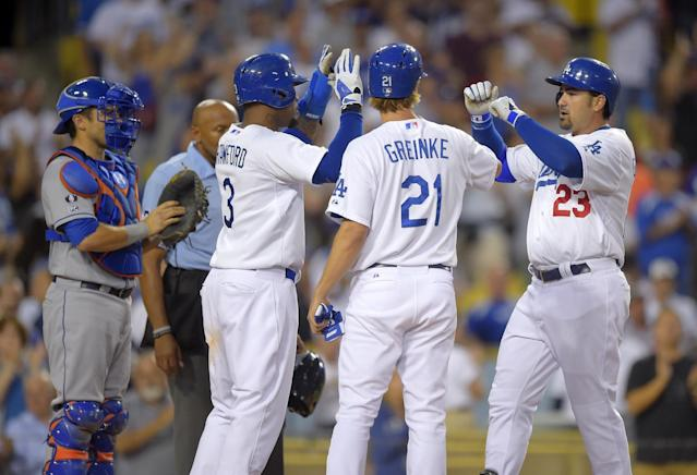 Los Angeles Dodgers' Adrian Gonzalez, right, is congratulated by Zack Greinke, second from right, and Carl Crawford after hitting a three-run home run, as New York Mets catcher Travis d'Arnaud waits during the fifth inning of a baseball game, Saturday, Aug. 23, 2014, in Los Angeles. (AP Photo/Mark J. Terrill)