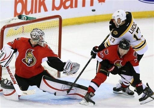 Boston Bruins Milan Lucic (17) attempts to deflect a flying puck as he is cheked Ottawa Senator Sergei Gonchar (55)during second period NHL hockey action in Ottawa Monday March 11, 2013. (AP Photo/The Canadian Press, Fred Chartrand)