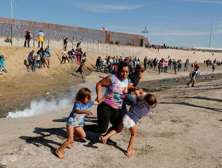 Maria Meza, a 40-year-old woman from Honduras traveling as part of a caravan of thousands from Central America to the United States, runs away from tear gas with her 5-year-old twin daughters Saira Mejia Meza and Cheili Mejia Meza. (Photo: Reuters)