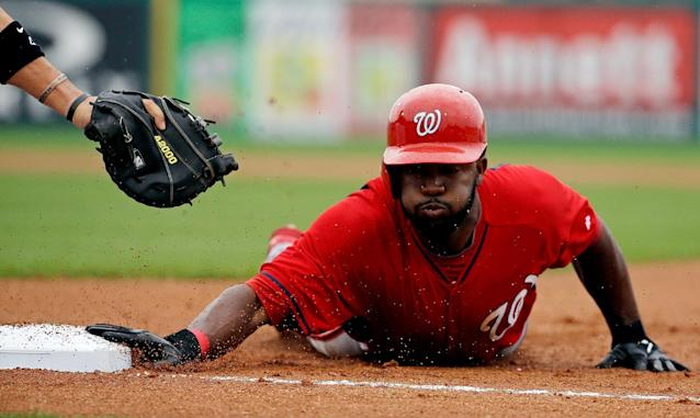 Washington Nationals' Denard Span, right, dives back to first base as he's picked off on the throw from Miami Marlins starting pitcher Tom Koehler to first baseman Garrett Jones, left, in the first inning of an exhibition spring training baseball game, Monday, March 24, 2014, in Jupiter, Fla. (AP Photo/David Goldman)