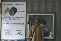 """A medical worker in a booth takes a nasal sample from a man at a coronavirus testing site in Seoul, South Korea, Tuesday, July 6, 2021. The sign at left reads: """"How to collect COVID-19 samples."""" (AP Photo/Ahn Young-joon)"""