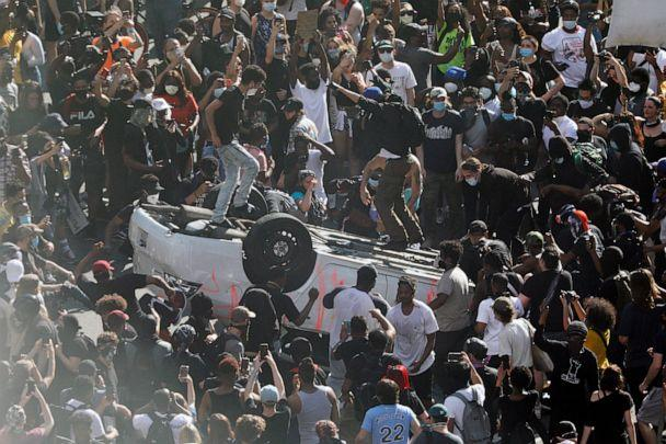 PHOTO: Protesters jump on a car they overturned near the Municipal Services Building in Philadelphia during a Justice for George Floyd rally Saturday, May 30, 2020. Floyd died in Minneapolis police custody on May 25. (Elizabeth Robertson/The Philadelphia Inquirer via AP)