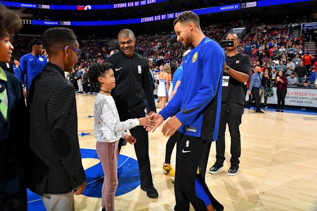 Steph Curry meets a crying fan before the Warriors' win over the 76ers on Saturday. (Getty)