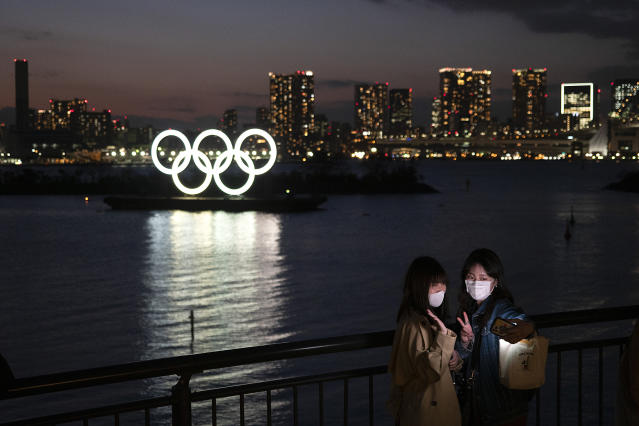 "Two women take a selfie with the Olympic rings in the background in the Odaiba section of Tokyo, Thursday, March 12, 2020. Tokyo Governor Yuriko Koike spoke Thursday after the World Health Organization labeled the spreading virus a ""pandemic,"" a decision almost certain to affect the Tokyo Olympics. For most people, the new coronavirus causes only mild or moderate symptoms. For some it can cause more severe illness. (AP Photo/Jae C. Hong)"