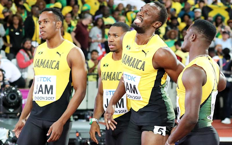 A grimacing Usain Bolt is helped by his Jamaica team-mates - EPA