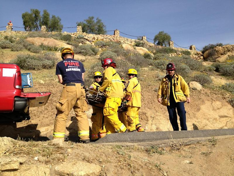 This March 25, 2013 image provided by the Riverside Fire Department shows rescue officials transporting a man found Monday on Mount Rubidoux in Riverside, Calif. The unidentified hiker apparently fell between some rocks. The man may have been there overnight or up to four days because he was severely dehydrated, although he was alert. (AP Photo/Riverside Fire Department)